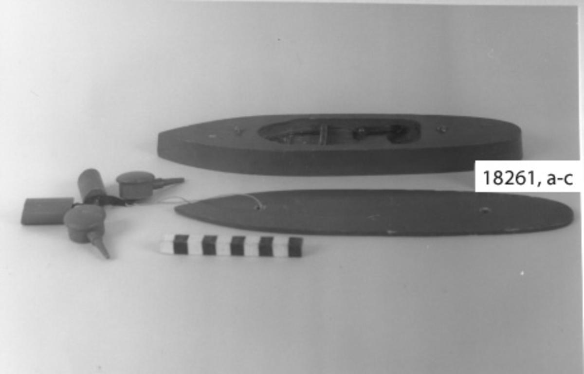 Leksaksbåt av trä i form av pansarbåt målad i grått. Bestående av tre olika delar a: skrov, :b däck, :c skorstenar och artilleripjäser. ;a skrov H= 23 mm, L= 298 mm, B=72 mm Skrovet i ett stycke med spetsig för, vinklad utåt vid vattenlinjen och rundad akter. Plan botten. Invändigt urholkning med mekanism liknande råttfälla. En spiralfjäder spänner en bygel som vid tryck på en klapp placerad på båtern utsida midskepps utlöses. Röd knapp, runt denna flertal hål som visar var projektilerna missat. Vid träff på knappen flyger däck, artilleripjäser och skorstenar iväg!