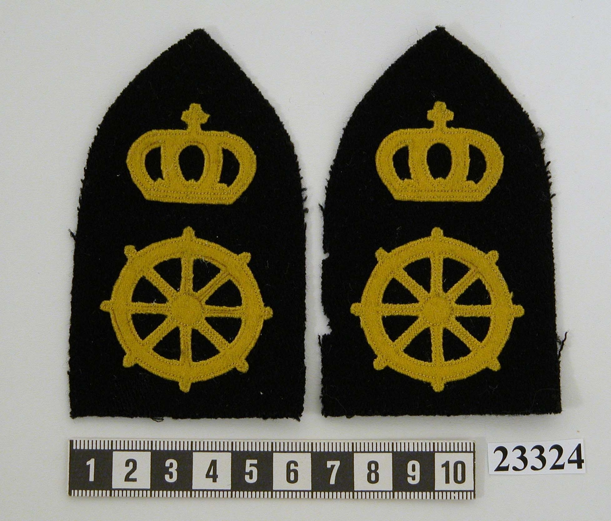 Granatformad yrkesbeteckning (ett par) i svart textil försedd med ratt (vilken betecknar däckslinje) samt krona i gult kläde. Båda tecknen är fastsydda med gul tråd.
