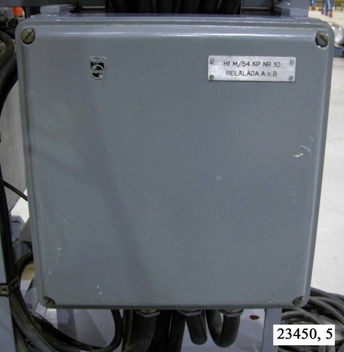 """Rektangulär, grålackerad och slät box av metall. I respektive hörn sitter bultar. I relälådans högra hörn sitter en metallbricka försedd med texten """"Hf M/54 KP NR 10, RELÄLÅDA A o. B"""". I relälådans underdel sitter ett antal kablar fästa. Relälådan är monterad på ett hydrofonstativ, nere till höger på stativets baksida.  Not: Kablaget är ej medräknat i dimensionerna."""