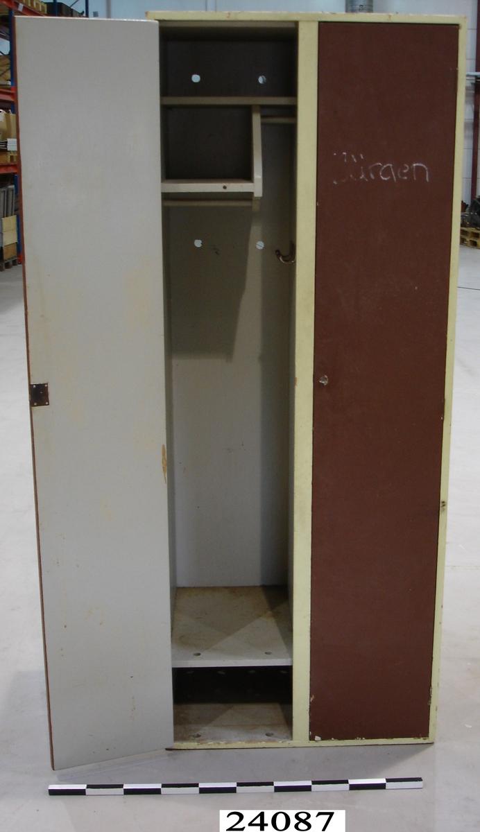 """Dubbelt logementsskåp av trä. Ljusgrått målade sidor och insida. Kanten runt  skåpsdörrarna är grön-gult målad. Skåpsdörrarna är brunmålade och försedda med lås och nyckel. I de bägge skåpen finns skohylla, två hyllor och två klädstänger. I vänster skåp finns tre klädkrokar.  Baksida av plywood vilken är försedd med ett antal ventilationshål. Ovanför vänster skåp finns numret """"2"""" och ovanför höger skåp """"3"""", skrivet för hand med röd spritpenna."""