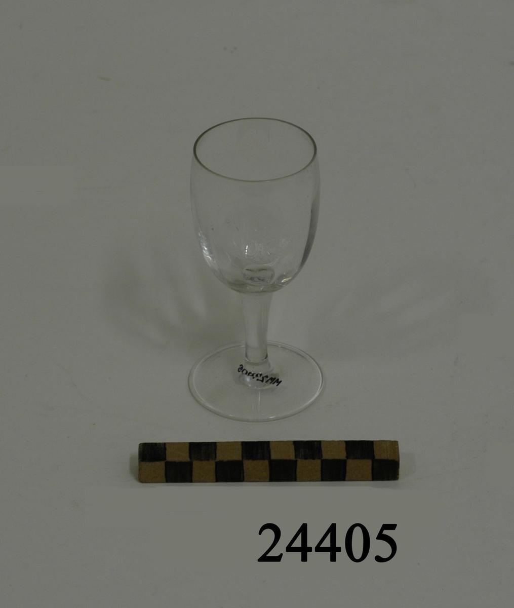 Likör eller sherryglas bestående av välvd smal cylindrisk kupa med lodräta vågmönster. Smalt runt ben och rund plan fot. På kupan graverad dekor: ett krönt stockankare med monogram R M ( Reale Marina = Kungliga Flottan ). Diameter:  47 mm, glaset   D = 54 mm fot