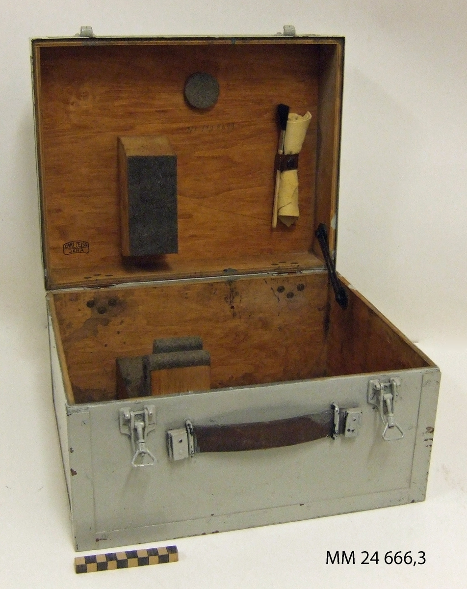"""Låda till målangivningskikare. Rektangulär gråmålad låda av trä. Spännen av metall och handtag av läderrem. I lådan finns även pensel och två sämskskinnstrasor, varav en ligger i förpackning av tillverkning """"Clarinol"""". Lådan stämplad: """"Carl Zeiss Jena"""" samt märkt med blyerts """"1989049""""."""