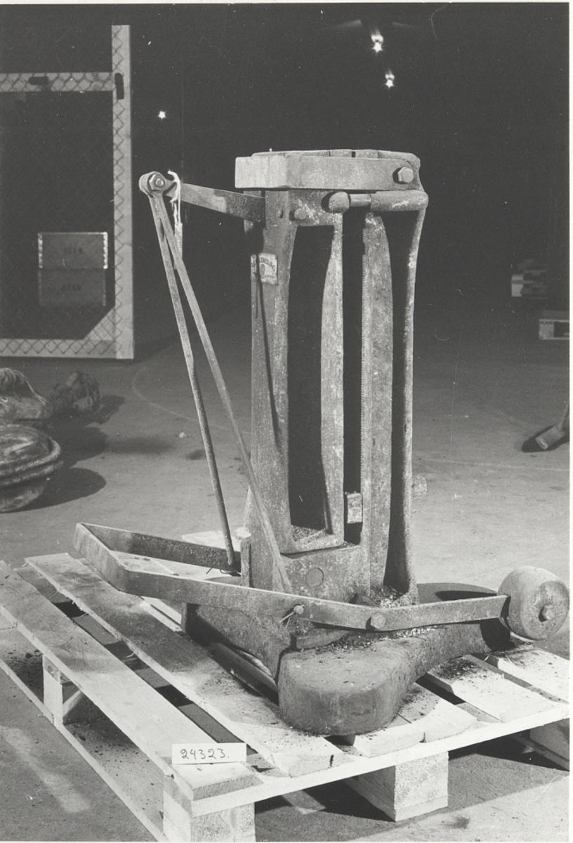 Två rektangulära ståndare; överstpress för tre bultdim. Pressen manövrerad med fottrampa med motvikt, klöverbladsformad fotplatta (60x60x60 cm)Presshuvud = 25 cm x 17 cm.