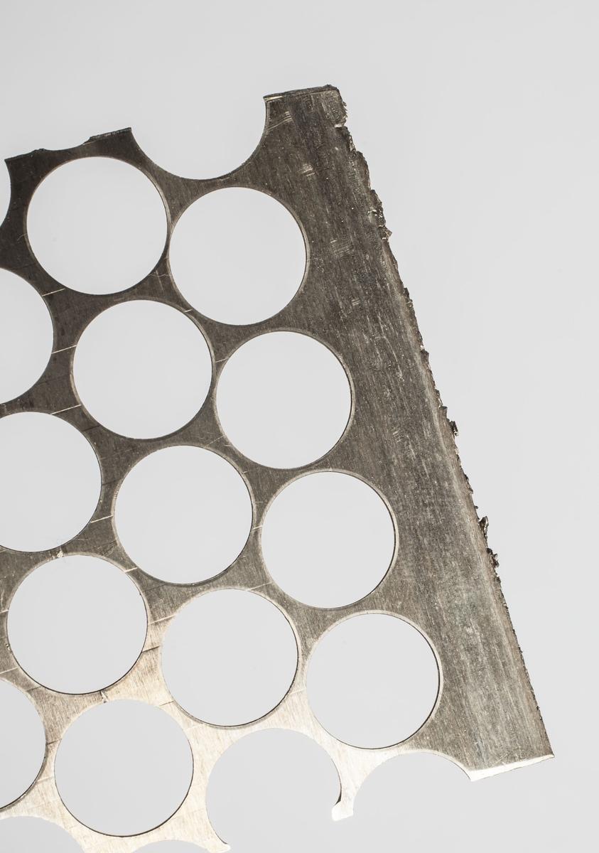 En flat, rektangulær metallplate med hull etter stansing.