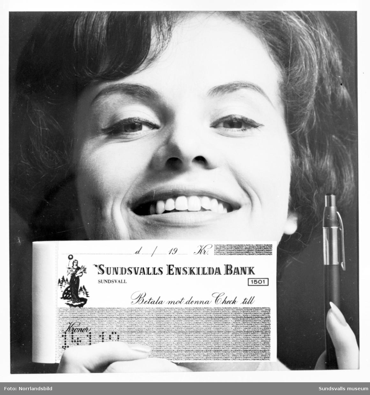 Reklambild för Sundsvallsbanken. En kvinna håller upp ett checkhäfte och en penna.