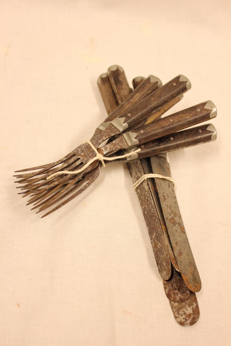 Gammelt bestikk. 5 kniver med brun/sort skaft, 5 gafler med brun/sort skaft, skaft, 4 kniver med gult beinskaft. Kniver og gafler med brun-sort skaft er litt rustne i kniven og gaffelen. Bein-kniver har ikke noe rust på kniven.