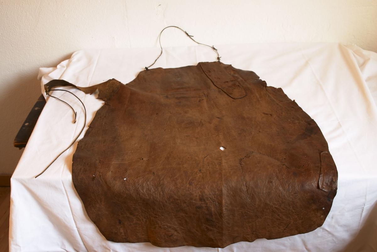 B: Skomakerforkle er skåret av et stykke lær og har en brunlig farge. Det har et lærtau øverst til å ha rundt halsen og to lærtau ett i hver side til å binde rundt livet. Bredde 53 cm, høyde 102 cm.