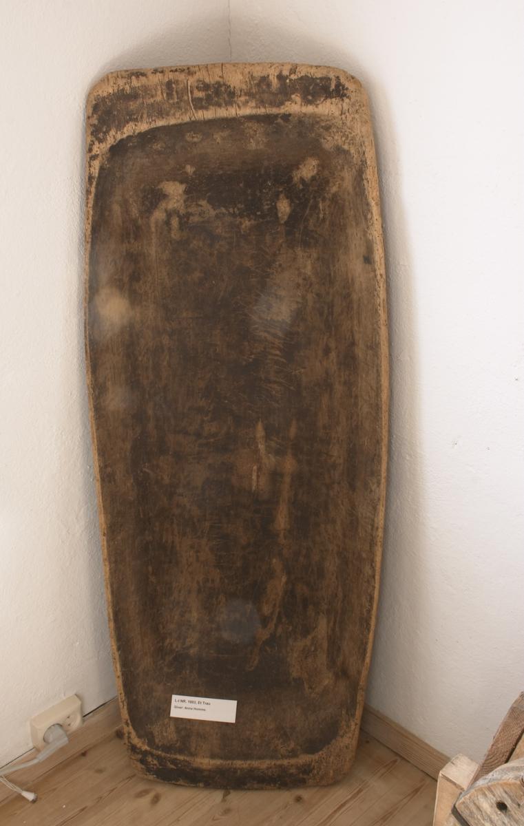Laget av et stort stykke tre - uthulet og en flate til handtak på hver langside. Rester av sort maling på utsiden og litt brunflammet på innsiden. Brukt til bl.a. å ha deig i ved baking. Brukt av Anna Hommes foreldre.