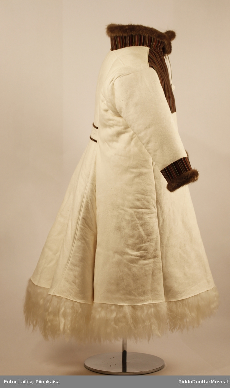 Ny dork, hudsiden vendt ut, ull 17-20 cm vendt inn. Brystpartiet av flerfarget fløyel. Halsstykke for beskyttelse mot kulde. Snorer av hvit sisti i halsåpningen foran. Spensel midt bak dekorert med firkanter med kråkesølv inni.