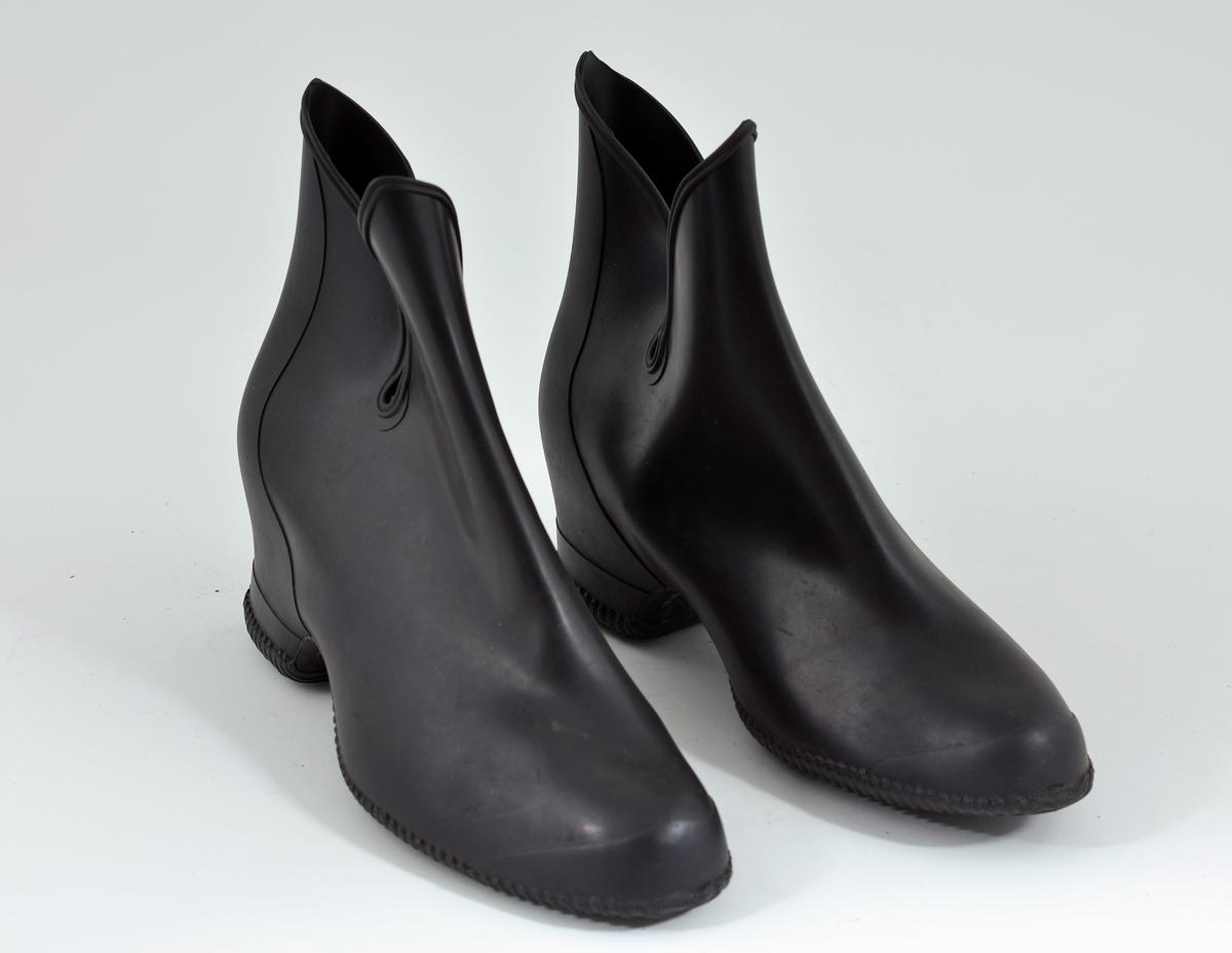 Svarte kalosjer av tynn gummi til å ha utenpå damesko. Halvhøy hæl.