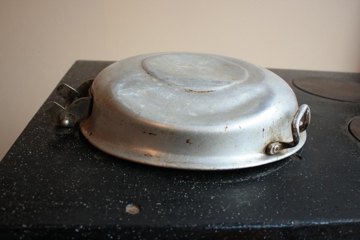 Komfyr med magasinrom og tre steikeplater. Lokk til å lagre på varmen og fem knappar til å regulere varmen