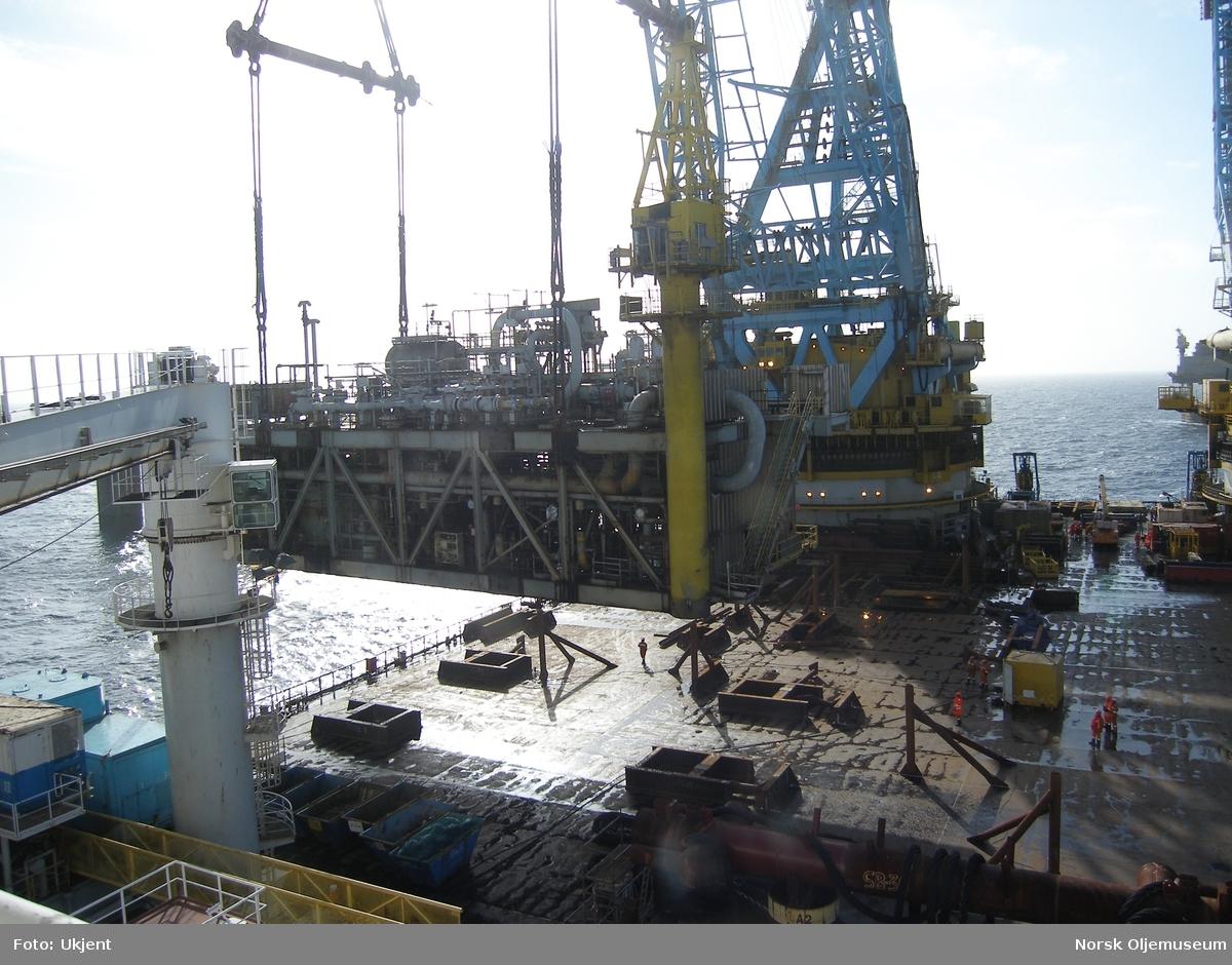 Kranfartøyet Saipem 7000 ligger ved TP1 og heiser modul for modul fra plattformen og ned på dekk, før de fraktes videre til opphogging og gjenvinning på land. Det er store dimensjoner over kran og løfteutstyret som brukes til slike store og tunge løft.
