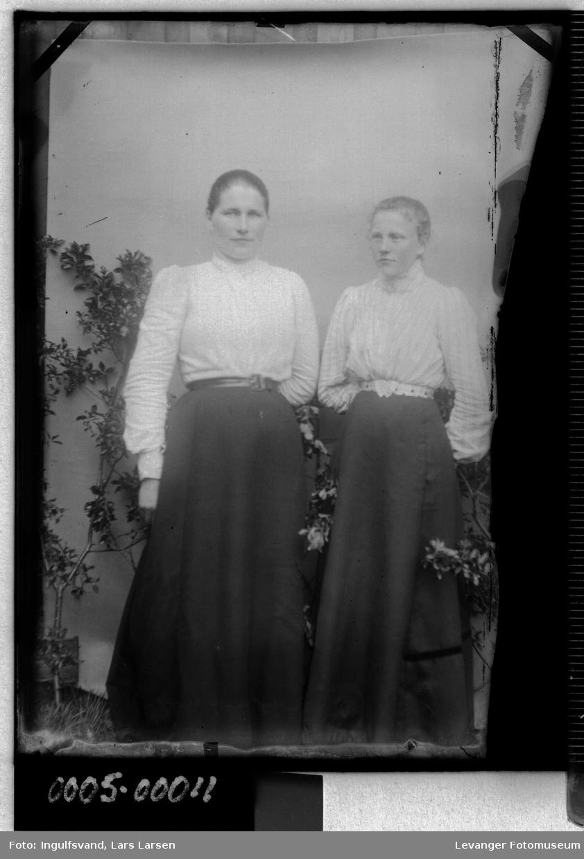 Portrett av to kvinner i halvfigur, med lyse bluser og mørke skjørt.