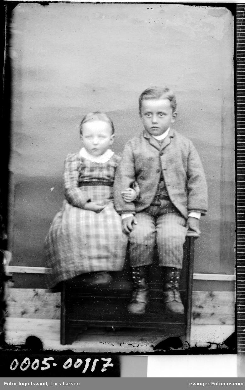 Portrett av jente og gutt som sitter på en kasse.