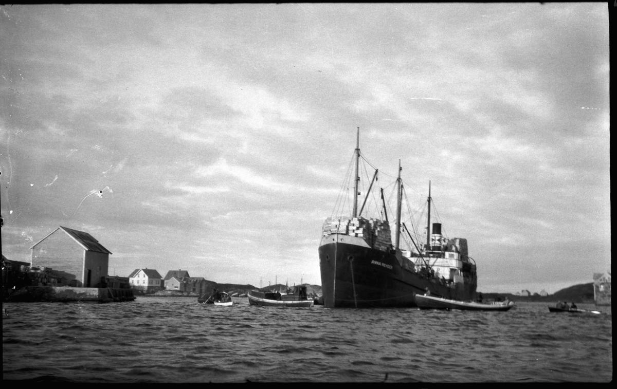 Ds Anna Rehder lastar storsild for nedising i Nikøy-osen, Bulandet. Fartøyet (1921/stål/brt:723) var eigd avr Carsten Rehder, Altona, Tyskland . Kjøpte opp storsild på Vestlandet vinteren 1939 for ising i kassar om bord. Silda vart eksportert fersk og nedisa til Europa. Her henta dei sild frå steng.  Kjelde om Anna Rehder:  http://www.skipet.no/NSS-Haugaland/215-SvIsesildfarten.html