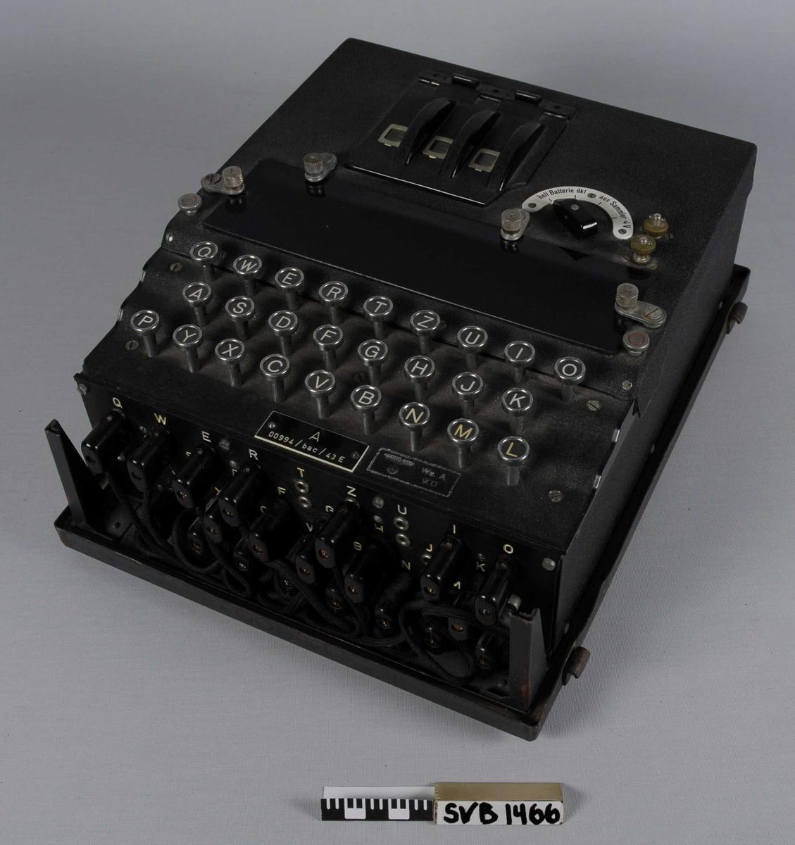 Tysk chiffreringsapparat. Enigma. Lokket inneholder erstatningsdeler;  31 lyspærer og 2 kabler, samt en innrammet 'hurtigveiledning'.