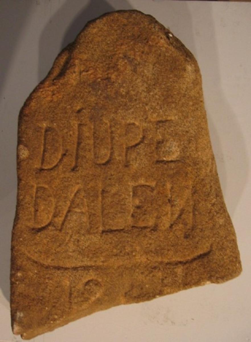 Fragment av en vägsten med texten ''Djupedalen''. Stenen, som troligen härstammar från 1800-talet, är funnen vid lågvatten på den torrlagda sjöbotten vid Djupedalsbäckens utlopp i Vänern, väster om Vänersborg. Förmodligen har den ursprungligen tjänat som vägsten då den återfanns invid den gamla stenbron som tidigare utgjorde del av den allmänna landsvägen från Vänersborg mot Dalsland.