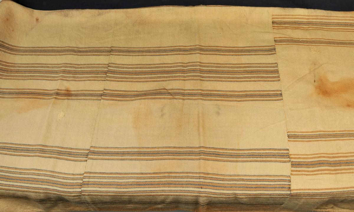 Tjeld av ull. Heimevove, kypert. Sydd saman for hand av tre delar. Ubleika, med striper i brunt og blått.