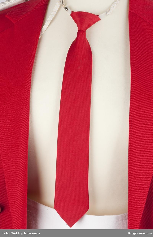 Slipset er enkelt røtt. Det er knute på det og festes rundt halsen med strikk og en plastanordning.