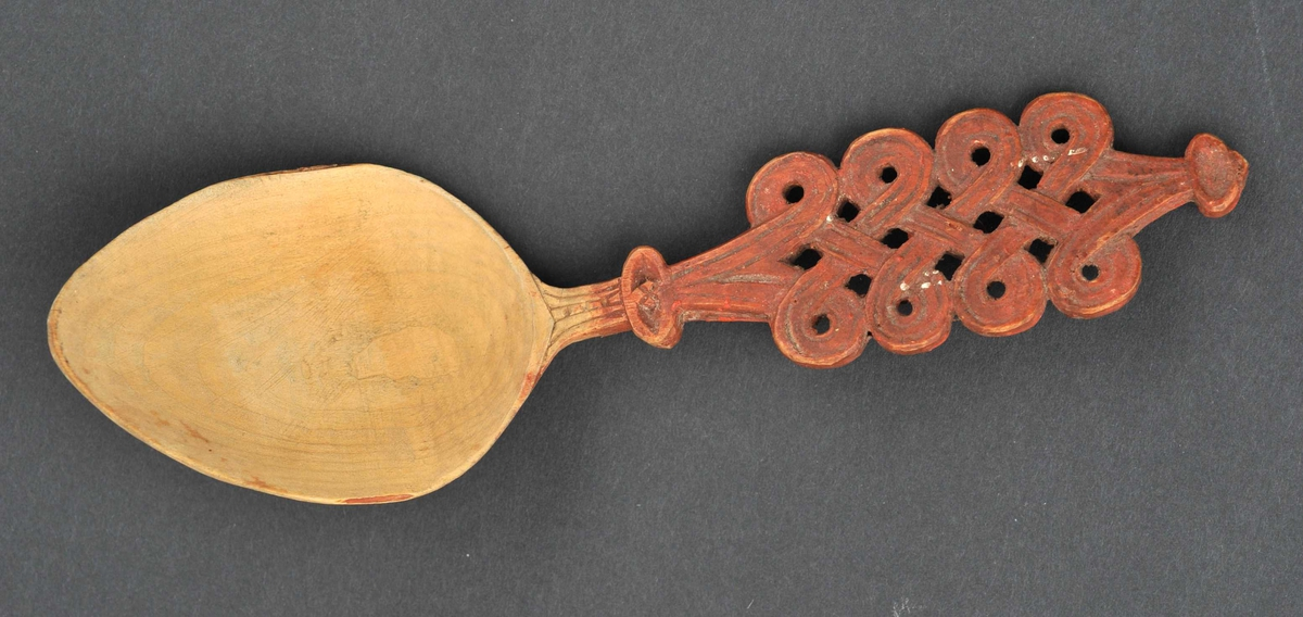 Eggeforma skeiblad. Handtaket er skore i gjennombrote mønster med dobbel valknuteform.