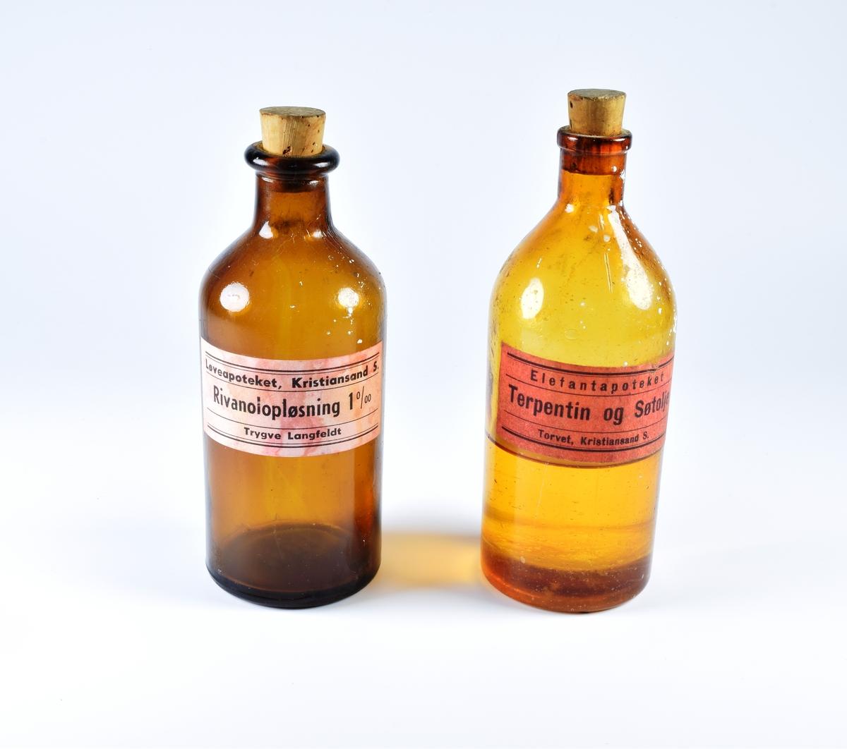 Syv sylindriske glassflasker i brunt glass med kork. Flaskene har ulik størrelse og fasong. Flere har rester av innhold.  a: Flaske med butte, avrundete skuldre og en sort og gul etikett med motiv av en dødningskalle. En tøyfille er trykket ned i flaskens hals.  b: Reseptflaske fra 1950 med hvit og blå etikett fra Svaneapoteket.  c: Flaske med slanke, avrundete skuldre med rosa etikett med sorte border og sort skrift. Flasken har inneholdt terpentin og søtolje.  d: Tom glassflaske med rosa etikett med sorte border og sort skrift. Flasken har inneholdt rivanoloppløsning.  e: Tom, liten glassflaske med riller på skulderene og uten etikett.  f: Liten glassflaske med to riller som går fra flaskens hals og ned. Rillene er plassert på hver sin side. Flasken har en rosa etikett med sorte border og sort skrift som er teipet på. Innholdet er bevart og flasken er nesten full.  g: Liten flaske med gummikork og rosa etikett med motiv av en hodeskalle og sorte border og sort skrift. Det er rester av innhold i flasken.