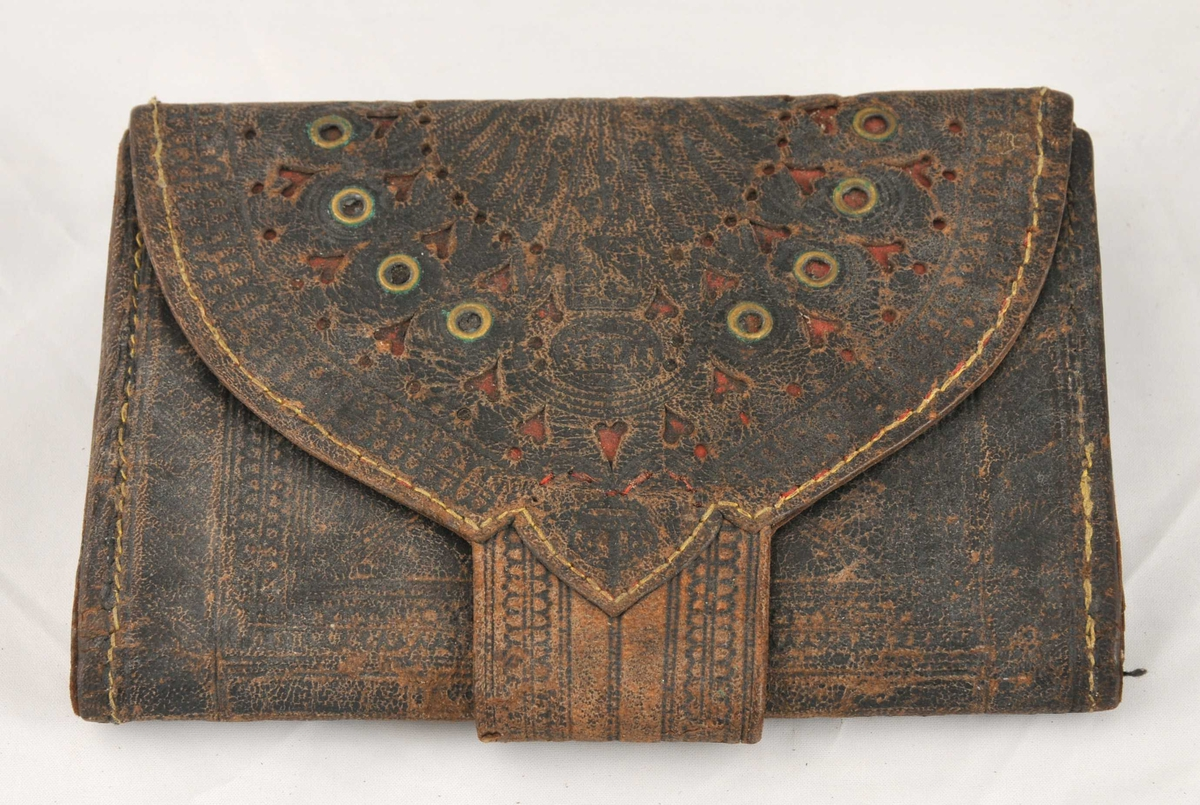 Lommeboka er særs forseggjort. Utvendig mørkt skinn med rik dekor. Påslåtte messingskiver. Innvendig lyst skinn med dekor. Lommeboka har 6 rom.