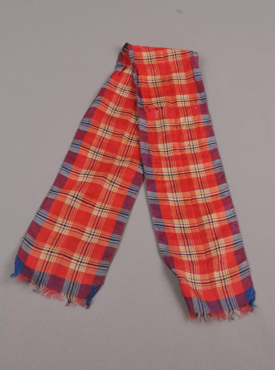 Rutete silkesløyfe i blått, raudt, gult og kvitt. Rektangulært, falda på langsidene og frynser i begge endar.