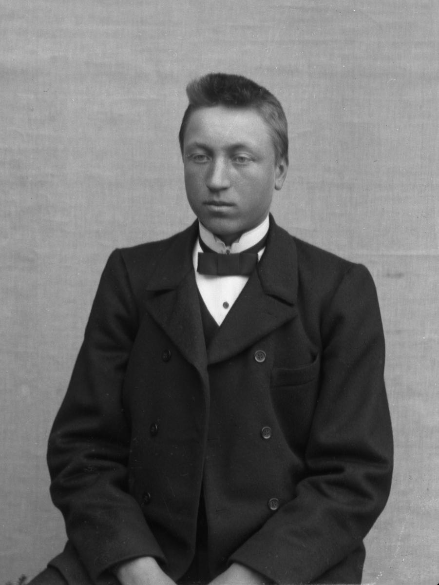 Ung dresskledd mann sittende foran hvitt lerret