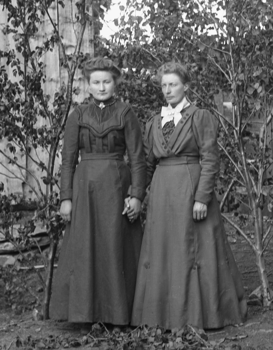 To kvinner i helfigur kledd i mørke kjoler, som holder hverandre i hånda, foran husvegg og bjørkekvister