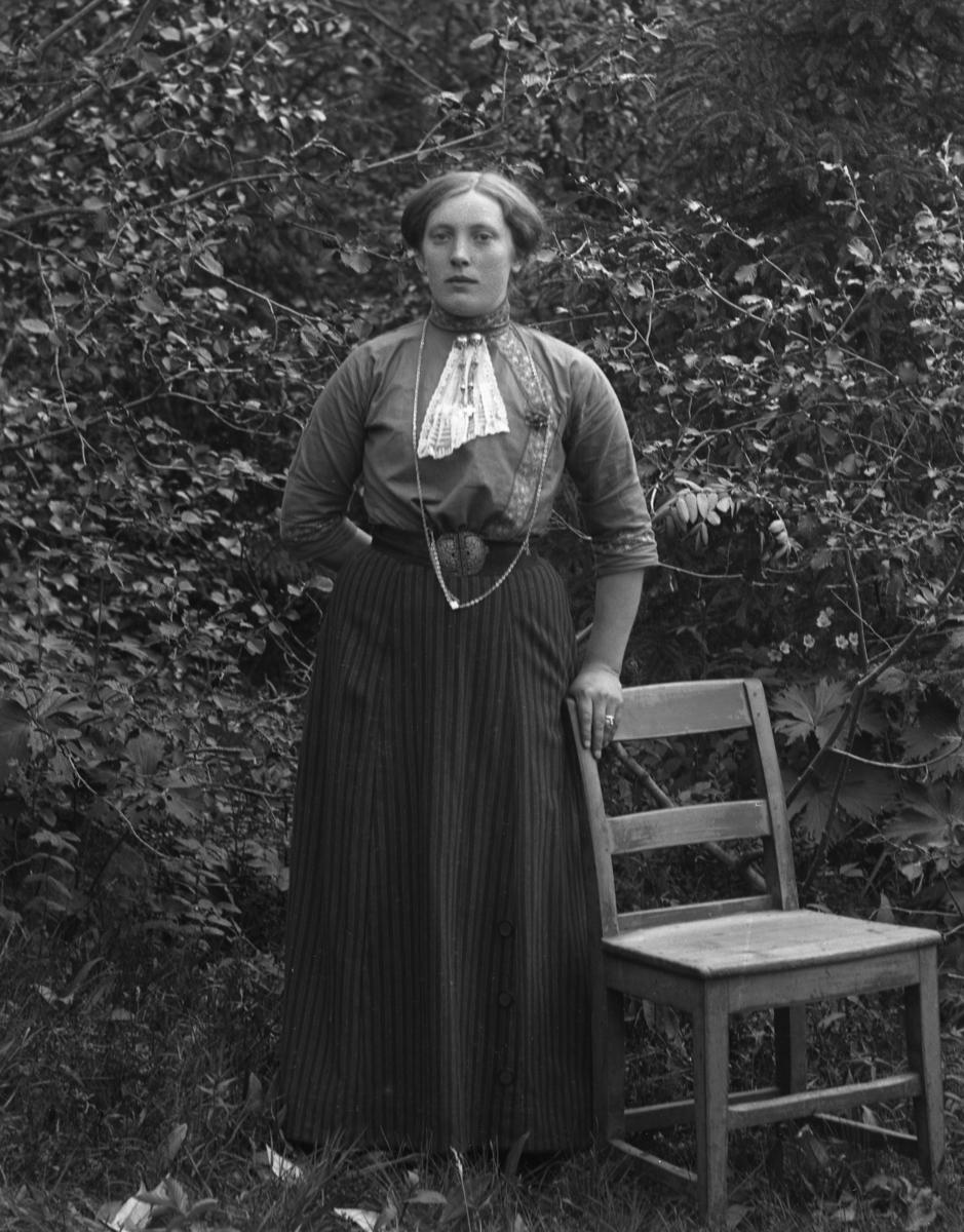 Kvinne i helfigur med stol, fotografert foran trær