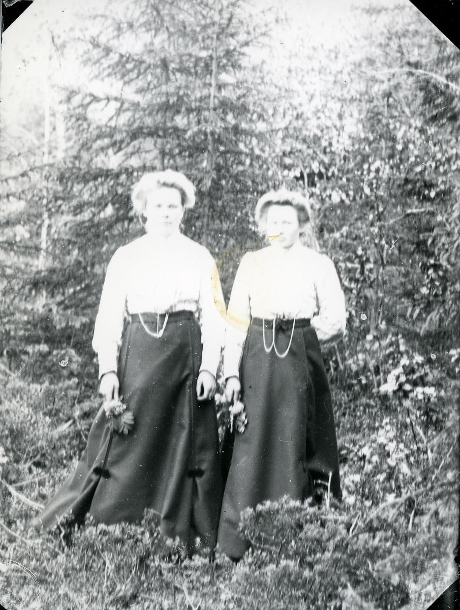 To kvinner, i helfigur, med blomsterbuketter. Avbildet i skog.