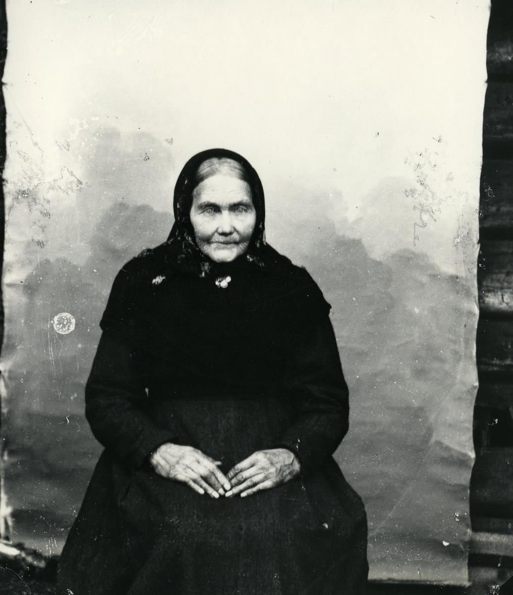 Eldre kvinne med skaut, sittende foran lerret
