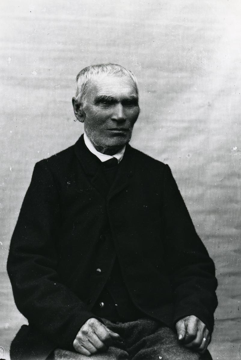 Eldre mann sittende foran lerret
