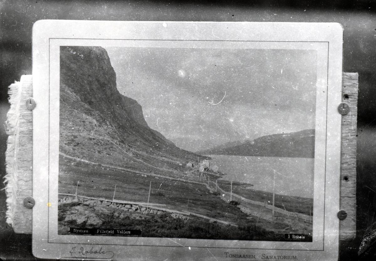 Postkort festet på treplate. Landskap med fjell, vei, innsjø og bygninger