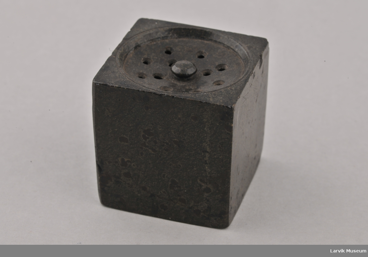 Kube med en sirkel form på toppen, i denne huller.