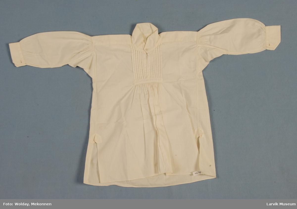 """Form: Liten barneskjorte, med """"kina"""" krage med to """"knappehull"""", vertikale legg på brystet, rynker under legg. Ermer lange, med rynker på skuldrene. Spesielt fint sydd, med RA brodert inn ned til venstre, der en trekant stikker ut."""