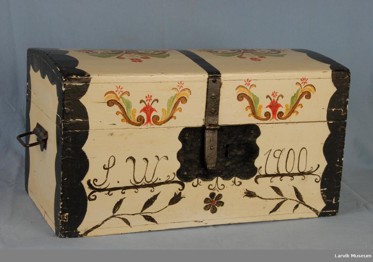 Form: Rektangulær, med buet lokk. Lås foran, Håndtak i sidene.