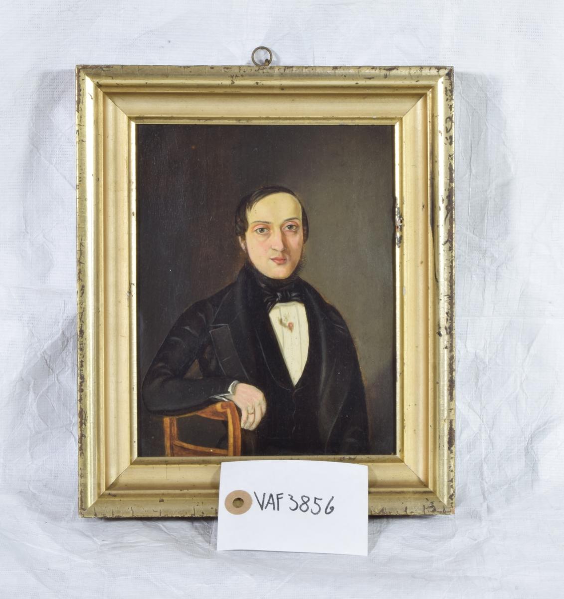 Lite portrett av en mann i sort drakt.