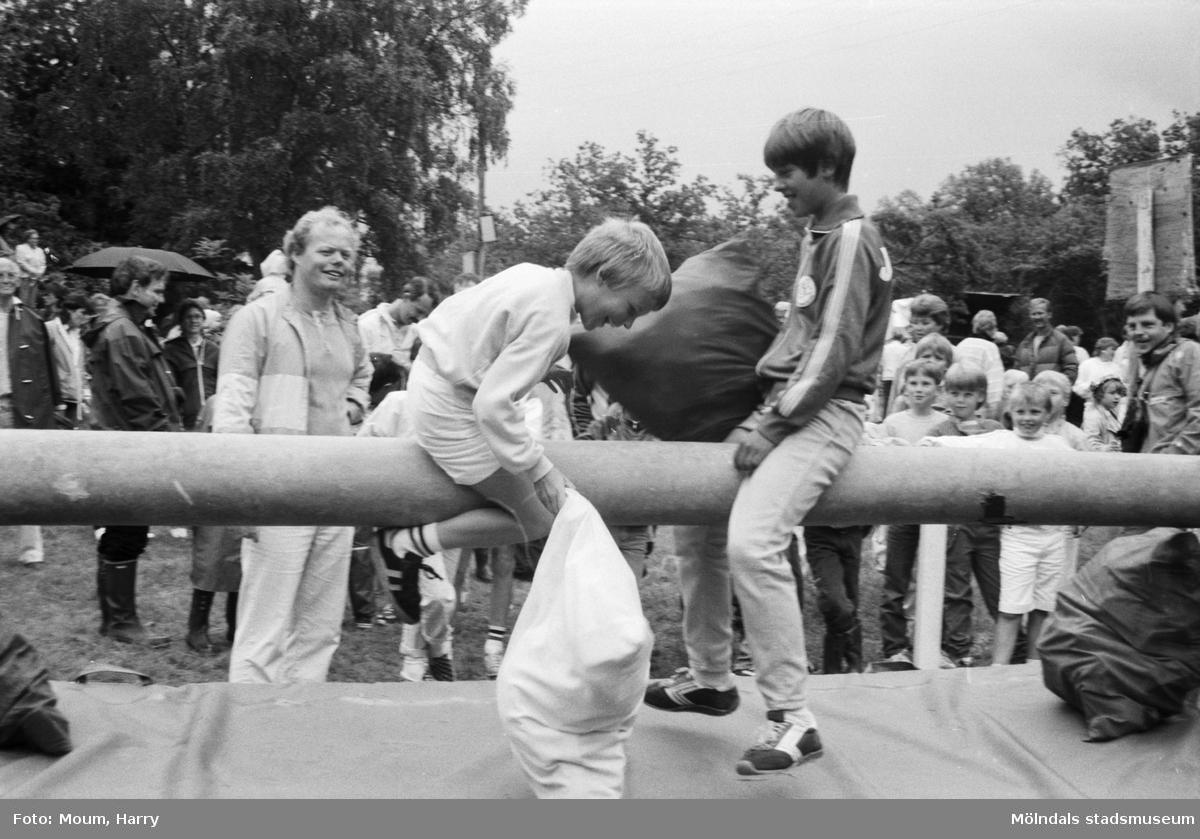 """Midsommarfirande på Ekensås i Kållered, år 1984. """"Pojkarna slogs så det stod härliga till på den såphala stången i sitt kuddkrig.""""  För mer information om bilden se under tilläggsinformation."""