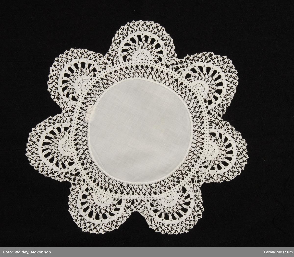 Form: midtfelt av hvit cambric,diam. ca. 13 cm,blonde