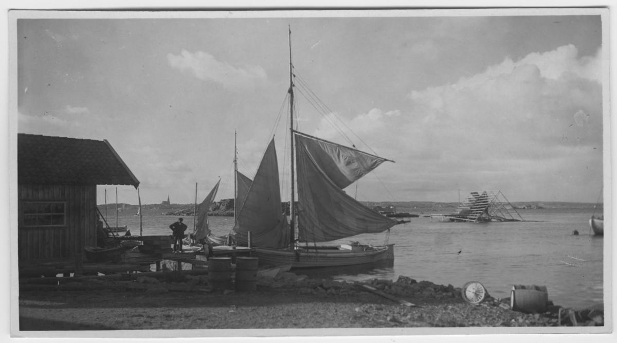 'Henrikssons brygga, Lysekil i fonden N.N.V Båtar vid brygga, 1 man står på bryggan. I vattnet torkställning för fisk. ::  :: Serie fotonr 1888-1963.'
