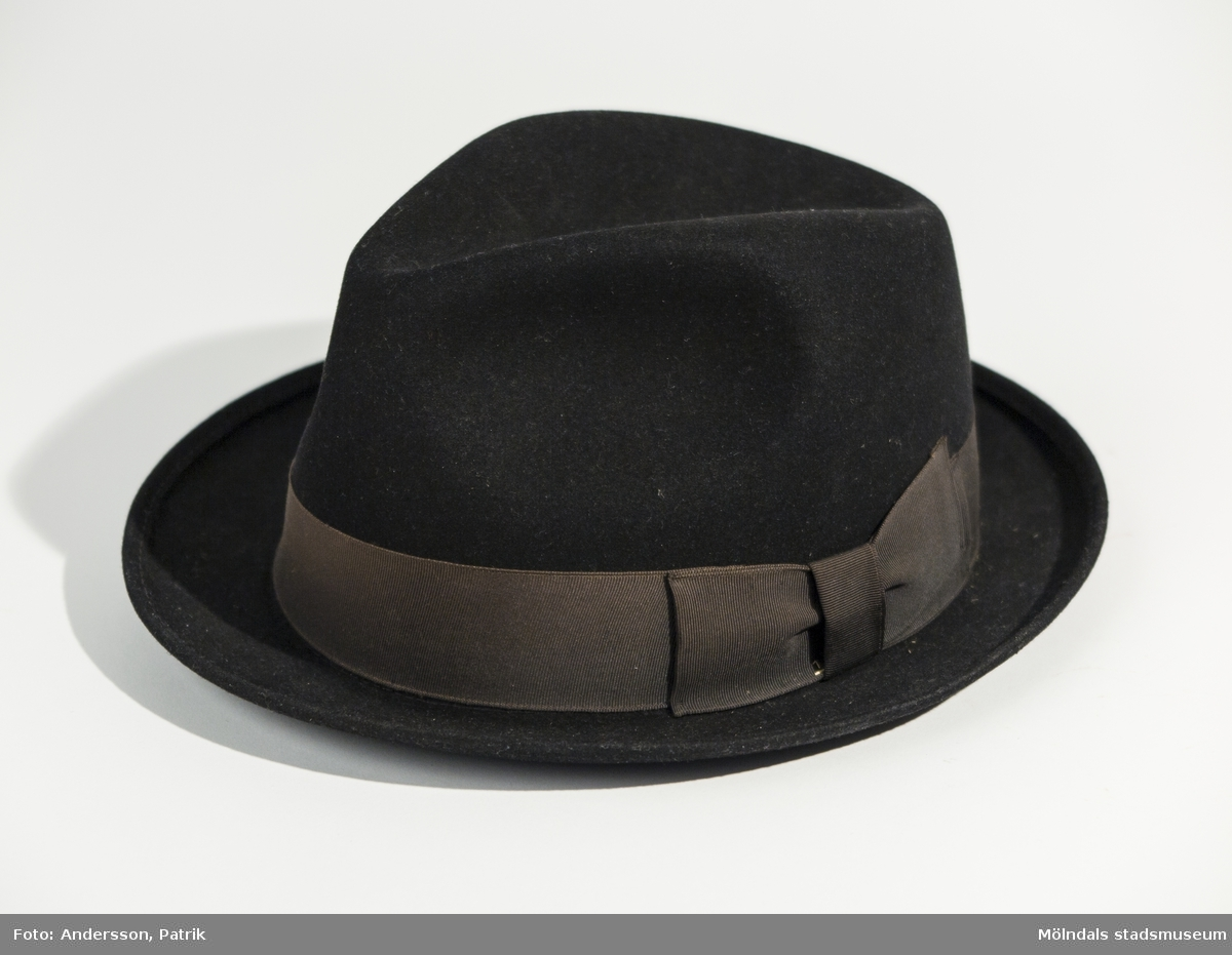 Svart hatt i stl. 57 av sammet med ett sidenband runt om. Hatten är inköpt på Bröderna Petterssons herrekipering i Mölndal, före 1972.