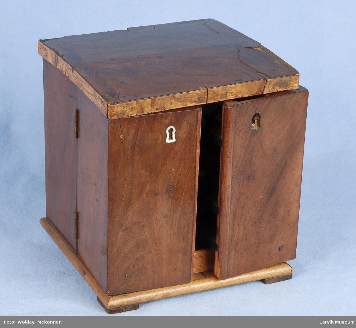 """Form: kvadr.boks i lukket tilstand. dobb.dør. to nøkkelhull hvorav ett """"falskt"""" lokket må løftes for å åpne dørene. dører hengslet midt på sider, lokk hengslet i bakkant. hull for 36 sigarer.."""