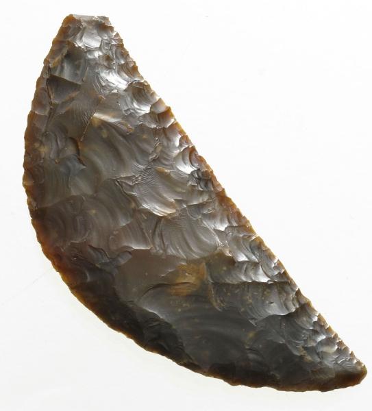 Sigd av mørk brun, spettet flint, av typen H. Gjessing: Rogalands Stenalder, fig. 235, men smalere. Den ene spissen mangler, men ellers godt bevart og pent forarbeidet. Eggen har den karakteristiske blanke overflaten, som tyder på at stykket er brukt til skjæring av korn.