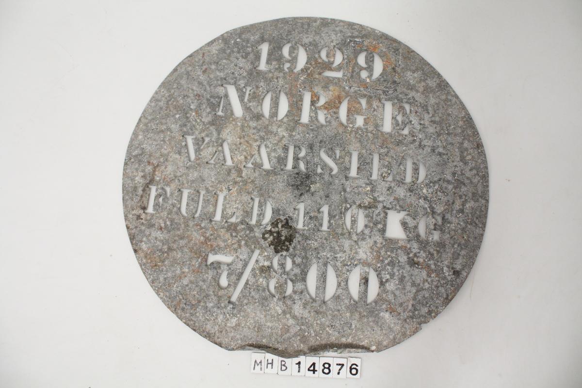 Sirkulærtformet tønnemerke. Et metallhåndtak på rettsiden.