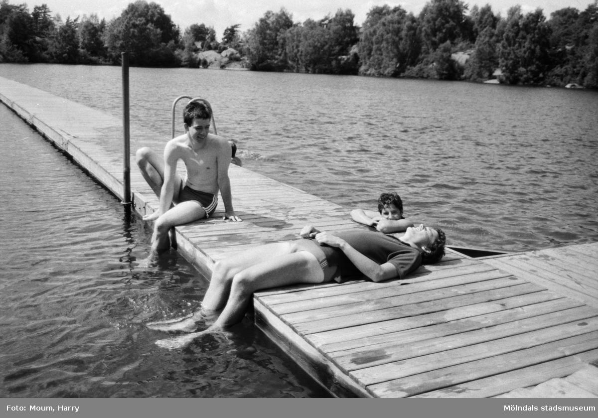 """Bergsjöns badplats i Kållered, år 1983. """"Ända från Wohltorf i Västtyskland kommer den här trion och njuter i fulla drag vid Bergsjön.""""  För mer information om bilden se under tilläggsinformation."""