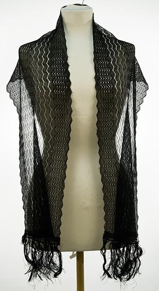 Rektangulært, langt sjal med lange frynser på kortsidene. Mønstret med horisontale og vertikale striper.