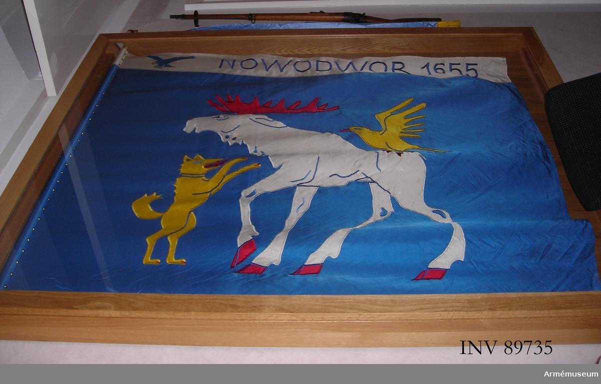 På blå duk landskapet Jämtlands vapenbild: en gående vit älg, angripen på ryggen av en luftande falk och framifrån av en upprest hund, båda gula. Samtliga djur med röd beväring. På vid bård i fanans överkant segernamn i blått samt en flygande örn.