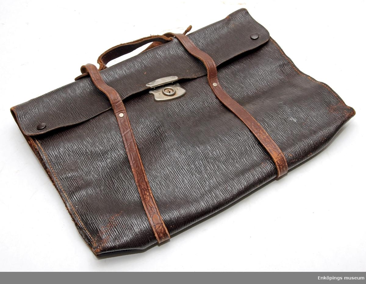 Svart portfölj av läder med knäpplås och handtag i läder.