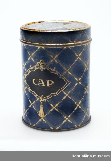"""Funktion: Förpackning till karameller """"CAP Familjeblandning"""" Burkens färg är blå med rutmöster i guldfärg. På framsidan av burken är ett svart varumärke med bokstäverna CAP. CAP Familjeblandning bestod av karameller med olika fyllningar av choklad, nötter, mandel samt olika sylter och med olika smaktillsatser; runda, ovala eller långsmala former. En pärlemorglänsande karamellmassa täckte de olika fyllningarna. Även marsipanbitar täckta med ett lager färgskimrande karamellmassa ingick i blandningen. I """"CAP 1895-1945; Halvsekelskrift"""" skriver man i kapitlet """"Hur CAP Familjeblandning kommer till"""" att produkten i de blå Familjeblandningsburkarna har funnits att tillgå för finsmakaren i 25 års tid. CAP står för Claes August Pettersson, som startade sin verksamhet 1895 under firma FRANSKA KONFEKTFABRIKEN C. August Pettersson. Företaget låg i Nordstan i Göteborg. Tillverkning och handel med karameller och konfektyrer. År 1909 användes för första gången CAP på företagets nyupptagning av kola. Andra produkter från företaget var Pompom, Turban, Limpa, Snabblunch, Raja chokladkola"""